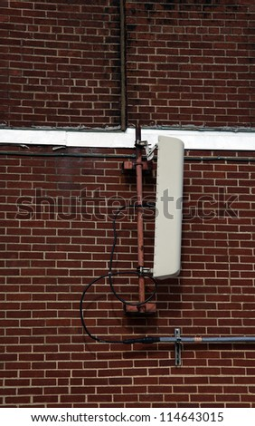 Cellular antenna mounted to the brick wall - stock photo