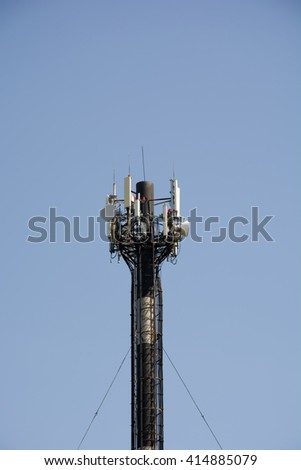 Cellular antenna on the chimney on the blue sky - stock photo