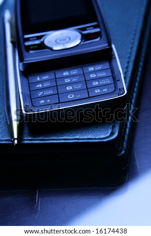 Cellular phone and pen on leather organizer