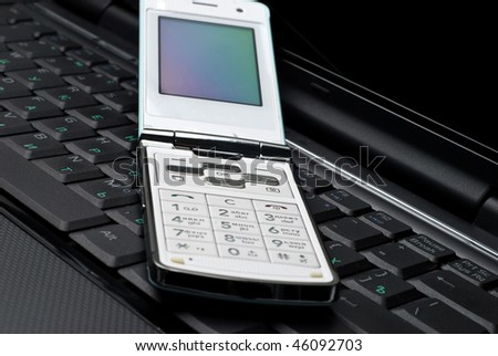 Cellular phone on a laptop