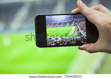 Cellular phone screen with football stadium field with teams playing game