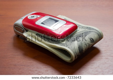 Cellular telephone with a pack of dollars - stock photo