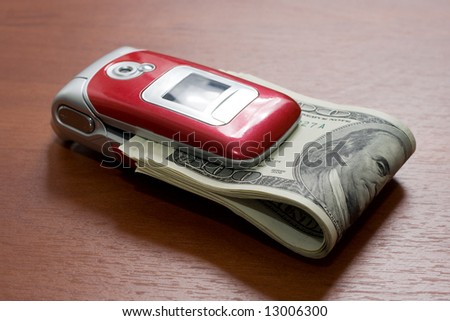 Cellular telephone with a pack of dollars on a table - stock photo