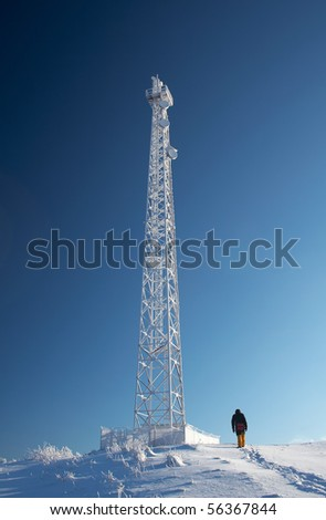 Cellular tower in snow on a blue sky background - stock photo