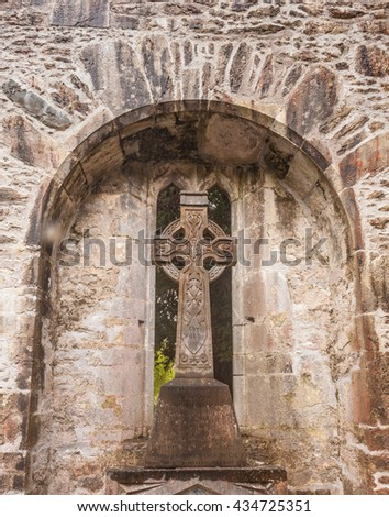 Celtic Cross in the archway of castle ruins in Ireland