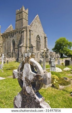 Celtic cross ireland, with an old abbey in the distance - stock photo