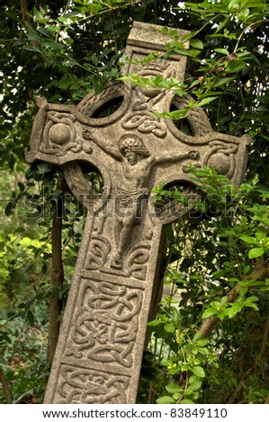 Celtic style cross with Jesus on the front.  Taken in English graveyard. - stock photo