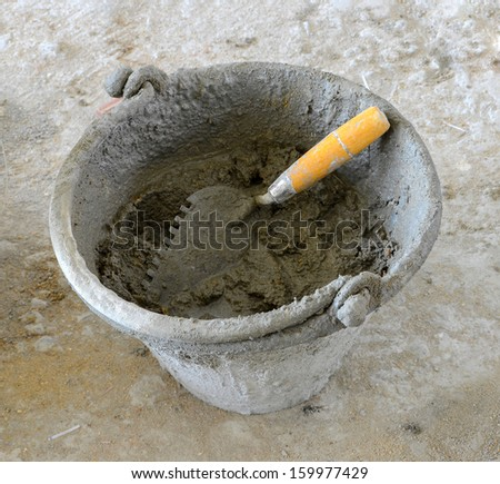 Cement and sand mixed with water and then put it in the can and trowel is a tool for spreading mortar and laying a try for tiling. - stock photo