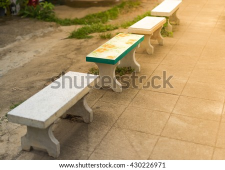 Cement bench in park. - stock photo
