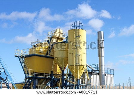 Cement factory machinery and a blue sky.