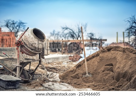 Cement mixer machine at construction site, tools and sand - stock photo