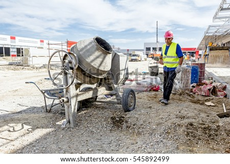 Cement mixer machine is at construction site with wheelbarrow, tools, sand and cement bag.