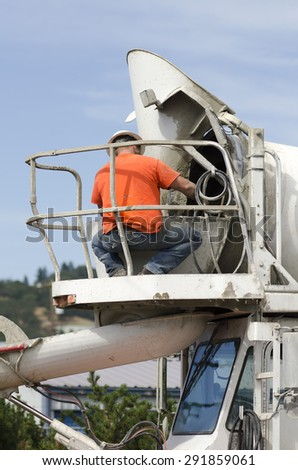 Cement mixer truck driver cleaning up concrete from chute following a delivery on a new road construction project - stock photo