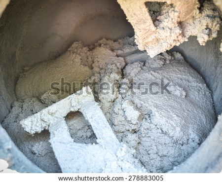 Cement or mortar is inside cement mixer. Cement or mortar is mixed on a construction site in an old electric cement mixer - stock photo