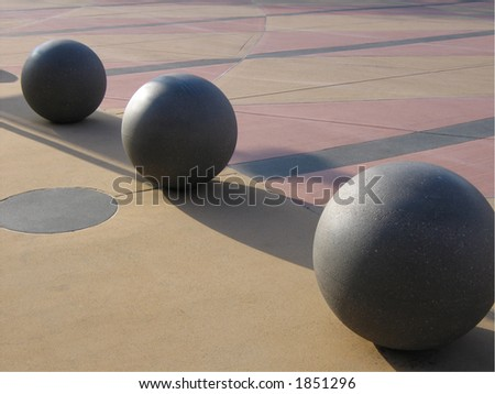Cement spheres in the entry plaza at the arena in Seattle lit by morning sunlight.