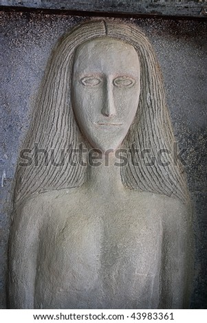 cement wall decoration of female torso