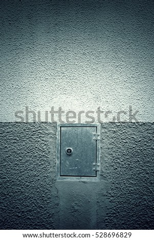 Cement wall with the door closed, detail of the city wall with a metal door, exterior texture background