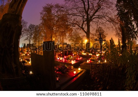 Cemetary decorated with candles for All Saints Day at night