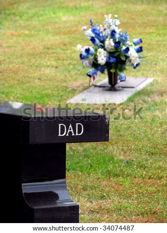 cemetery grave tombstone engraved with word dad - stock photo