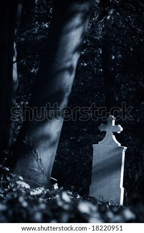 Cemetery, gravestone and tree in blue mood - stock photo