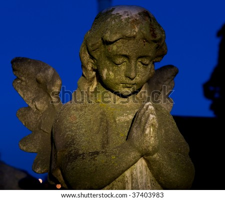 Cemetery headstone of a winged child angel or cherub with hand folded in prayer. - stock photo