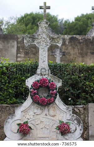 Cemetery monument with neverending porcelain roses has haunting appeal on a gray day in France. - stock photo