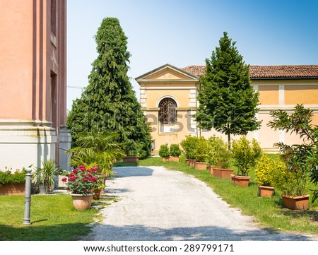 Cemetery near the rigid and severe architecture of the Shrine of Our Lady of Health of Solarolo in Italy, church from the 18th century devoted to the Blessed Virgin Mary - stock photo