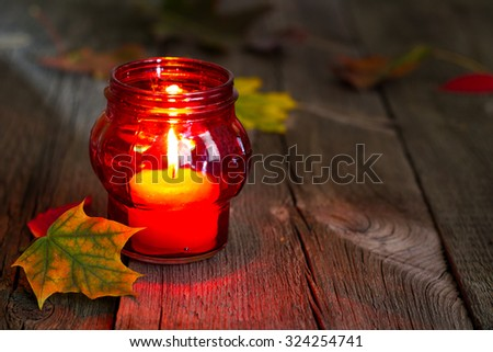 Cemetery red lantern candle with autumn leaves in night - stock photo