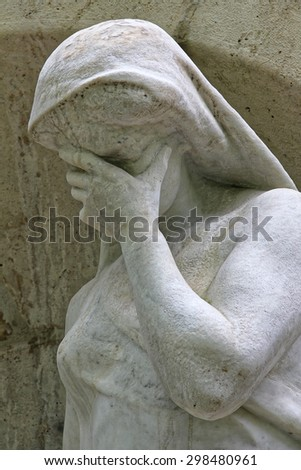 Cemetery statue symbolizing the sadness. - stock photo