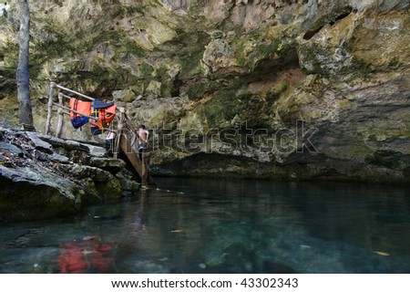 Cenote with crystal clear blue water and swimmers/hikers on the Yucatan Peninsula in Mexico - stock photo