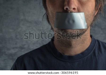 Censorship, adult caucasian man with duct tape on mouth to prevent him from speaking, freedom of speech and expression concept - stock photo