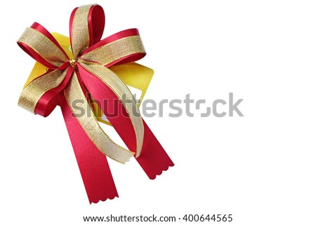 center of gold and red ribbon bow is attached on gold gift card (isolated and have clipping path) - stock photo
