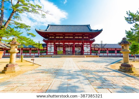 Centered red gate ro-mon front entry to Todai-ji, Todaiji, temple and walkway housing the Daibutsuden on a bright sunny blue sky morning in Nara, Japan. Horizontal copy space