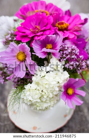 Centerpiece of garden flowers on a wooden table - stock photo