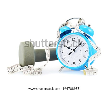 Centimeter tape, alarm clock and dumbbell composition isolated over the white background - stock photo