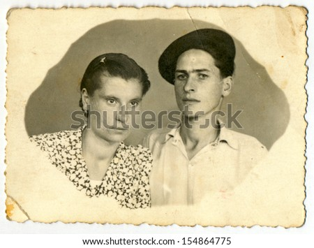 CENTRAL BULGARIA, BULGARIA - CIRCA 1950: Common photo of a young man and young woman (couple - husband and wife) - Note: slight blurriness, better at smaller sizes - circa 1950 - stock photo