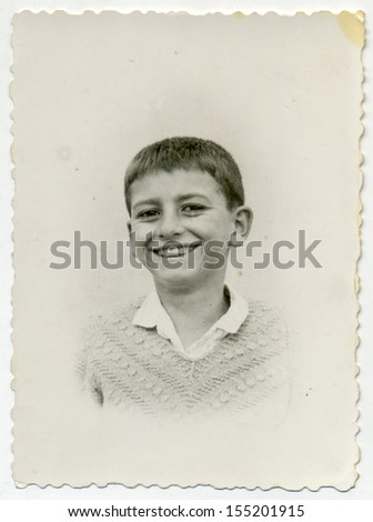 CENTRAL BULGARIA, BULGARIA - CIRCA 1955: Ordinary photo of an unknown laughing boy - Note: slight blurriness, better at smaller sizes - circa 1955 - stock photo