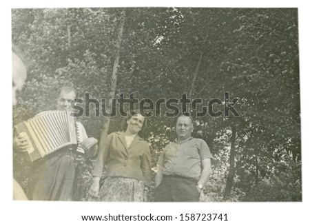 CENTRAL BULGARIA, BULGARIA - CIRCA 1955: the area Plovdiv - A man plays the accordion, other man and woman to obey him - Note: quite blurriness, better at smaller sizes - circa 1955