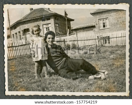 CENTRAL BULGARIA, BULGARIA - CIRCA 1955: the area Plovdiv - Uncle (younger man) and his unidentified niece before the old houses - Note: slight blurriness, better at smaller sizes - circa 1955 - stock photo