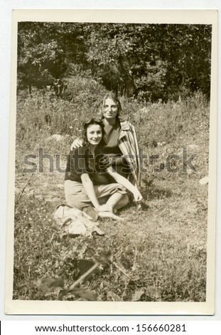 CENTRAL BULGARIA, BULGARIA, district Plovdiv - CIRCA 1970: Two young women sitting on a meadow. - Note: slight blurriness, better at smaller sizes - circa 1970