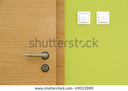 Central composition of wooden door and green wall - stock photo
