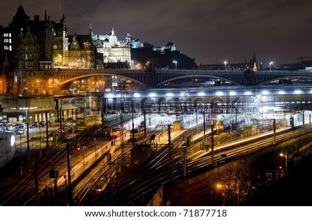 Central Edinburgh from Regent Road at night - vista including Waverley Train Station, North Bridge, Bank of Scotland building and Edinburgh Castle - stock photo