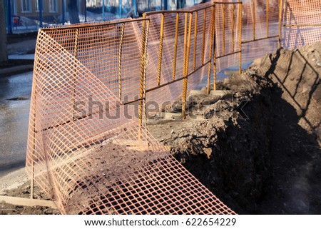 Central heating damaged pipe pit surrounded by the modern orange safety fence (polymeric mesh grid)