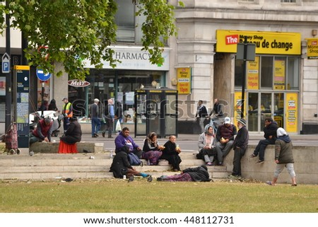 Central London England circa 2015; Group of Eastern European immigrants seating on steps and lying on the ground in Marble Arch area
