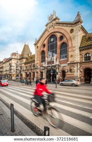 Central Market Hall in Budapest city, Hungary, Europe. Pedestrian crossing and cyclist in foreground, old building and blue sky in background.