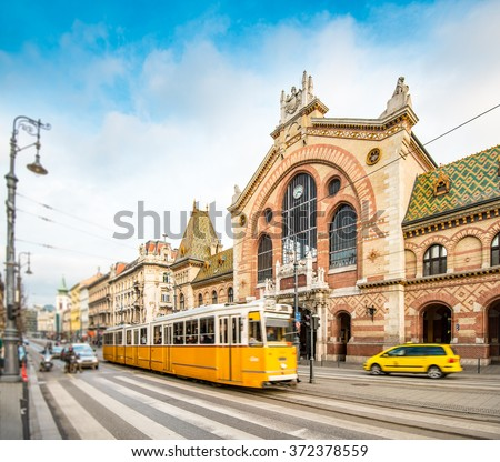 Central Market Hall in Budapest city, Hungary, Europe. Pedestrian crossing and yellow tram in foreground, old building and blue sky in background. - stock photo