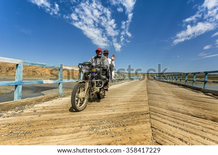 Central Mongolia, Mongolia - August 2015 -  Two Mongolian nomads riding a motorcycle over a wooden bridge.
