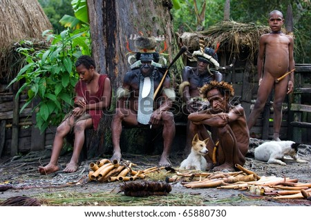 CENTRAL PAPUA NEW GUINEA , INDONESIA - JULY 2: New Guinean natives Dani of a tribe sit on a bench in Village of people Dani Dugum. Yali Mabel - Chief of Dani tribe.Papua New Guinea. July 2, 2009. - stock photo
