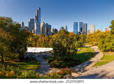 Central Park boasting its fall colors on a sunny day by Wollman Rink where New-Yorkers and visitors enjoy skating. View of Manhattan skyscrapers and buildings bordering the park. - stock photo