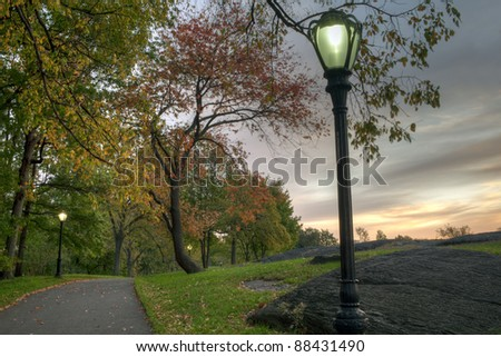 Central Park, New York City autumn scene in the early morning with street lamp and sidewalks - stock photo